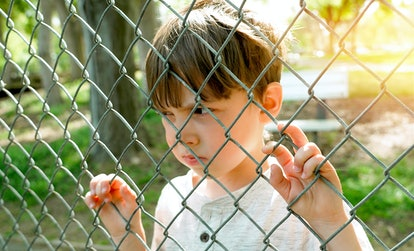 Caucasian Serious pensive Little boy looking through a schoolyard chainlink fence