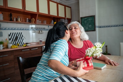 Photo of mature adult daughter giving a bouquet of ranunculus flowers and gift box to her senior mother for Mother's Day celebration. They are sitting on table in domestic kitchen. Shot with a full frame mirrorless camera.