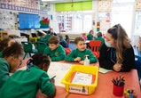 CARDIFF, WALES - MARCH 02: A teacher wearing a face mask speaks to children during a lesson at Bryn Hafod Primary School on March 2, 2021 in Cardiff, Wales. Children aged three to seven began a phased return to school in Wales from February 22. Wales education minister Kirsty Williams has said more primary school children will be able to return to face-to-face learning from March 15 if coronavirus cases continue to fall. (Photo by Matthew Horwood/Getty Images)