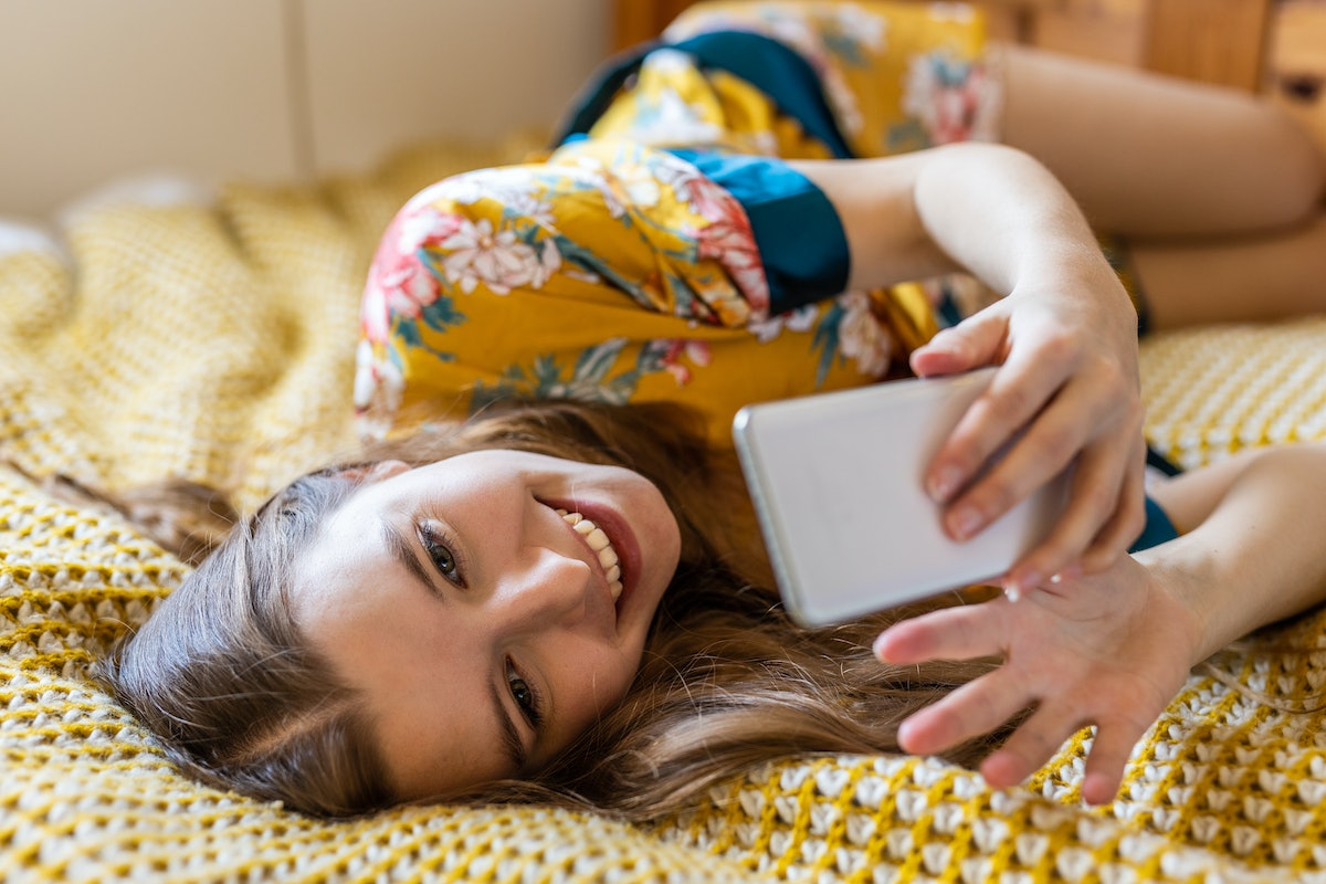 While smiling at a zoom meeting video conference a blond young woman in bed late in the morning holds her mobile phone