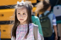 Hispanic elementary schoolgirl dreads the first day of school. She has a sad facial expression.