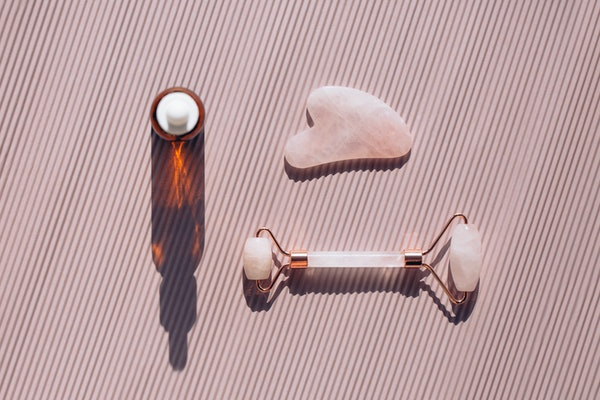 Rose quartz roller and guasha near glass bottle on striped pastel light pink background. Massagers are used for anti aging procedures with an oil or lotion. Sunlight makes shadows and illuminating reflections from bottle. Flat lay style with copy space