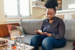 A woman sits on her couch measuring out supplements from a bottle. Experts explain the difference between prebiotics and probiotics.