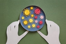 Conceptual paper illustration of human hands and coronavirus in a lab. Flat lay top-down composition...