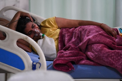 A Covid-19 coronavirus patient breaths with the help of an oxygen mask inside the Intensive Care Uni...