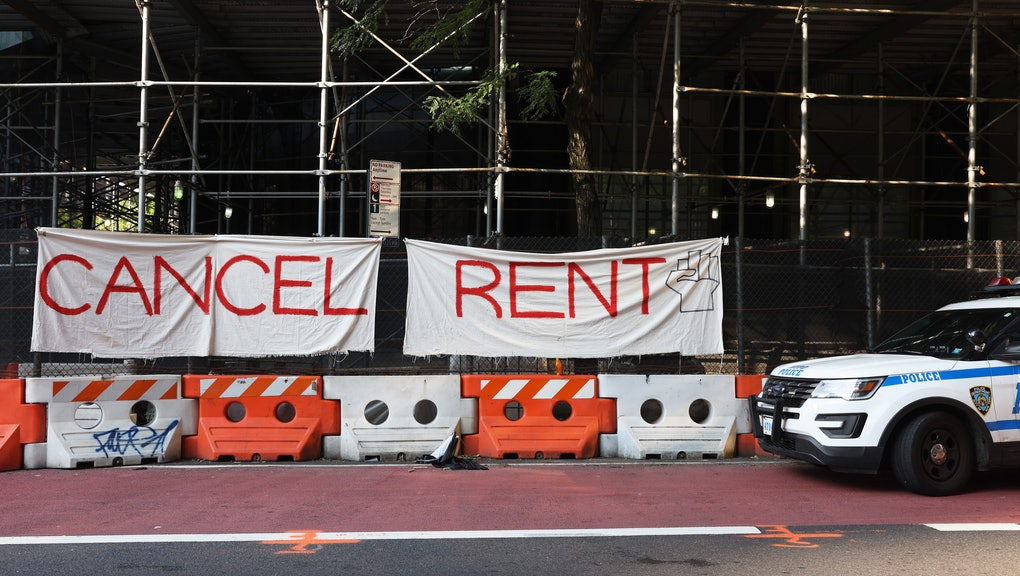 """NEW YORK, NEW YORK - AUGUST 10: A NYPD vehicle parks in front  of a """"Cancel Rent"""" banner hung up by participants of a 'Resist Evictions' rally to protest evictions on August 10, 2020 in New York City. The Right to Counsel NYC Coalition organized a day of action across New York City for tenants who are struggling to pay rent due to the COVID-19 public health crisis. Gov. Andrew Cuomo extended the eviction moratorium which ended on August 6, for an extra 30 days. (Photo by Michael M. Santiago/Getty Images)"""