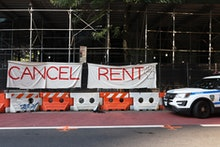 """NEW YORK, NEW YORK - AUGUST 10: A NYPD vehicle parks in front  of a """"Cancel Rent"""" banner hung up by ..."""