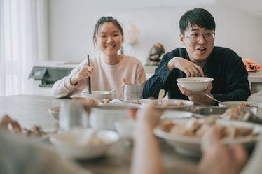 Asian chinese siblings enjoying family chinese new year reunion dinner having traditional dishes at ...