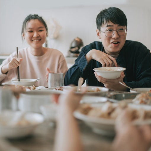 Asian chinese siblings enjoying family chinese new year reunion dinner having traditional dishes at dining table