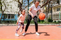 Photo of mother with her daughter playing basketball outdoors