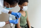 African-American, female injecting COVID-19 vaccine to a little black boy.  Shallow DOF, focus on a foreground