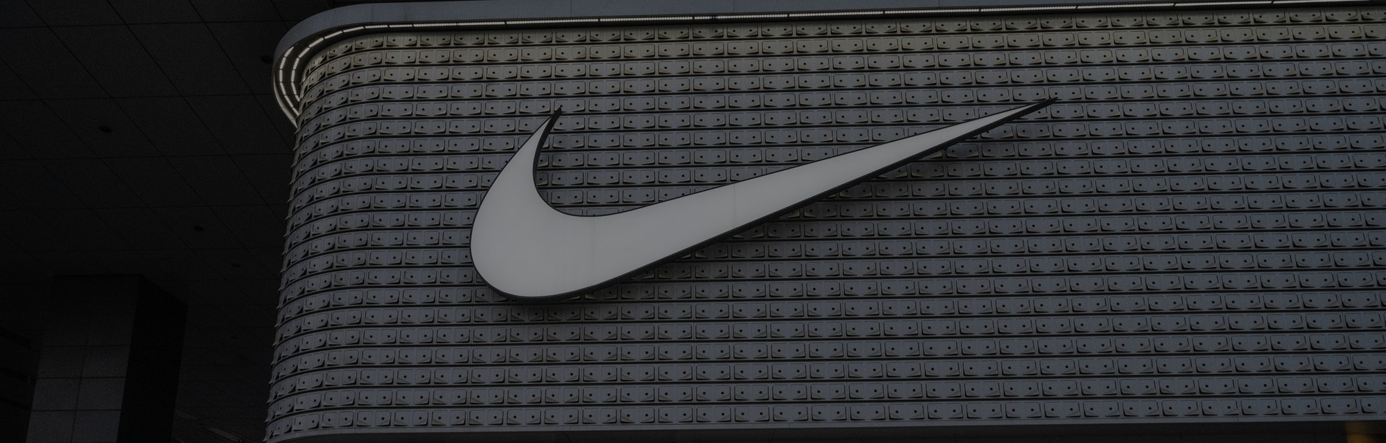 BEIJING, CHINA - APRIL 08: A woman walks outside a Nike store at a shopping area on April 8, 2021 in Beijing, China. (Photo by Kevin Frayer/Getty Images)