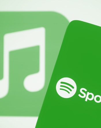 UKRAINE - 2021/04/18: In this photo illustration, the Spotify logo seen displayed on a smartphone screen in front of Apple Music logo in the background. (Photo Illustration by Pavlo Gonchar/SOPA Images/LightRocket via Getty Images)