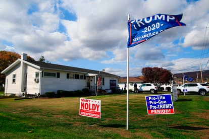 Signs and flags are displayed on the front lawn of a Trump supporter's house. Millennials with Trump-supporting parents are working to rebuild those relationships.
