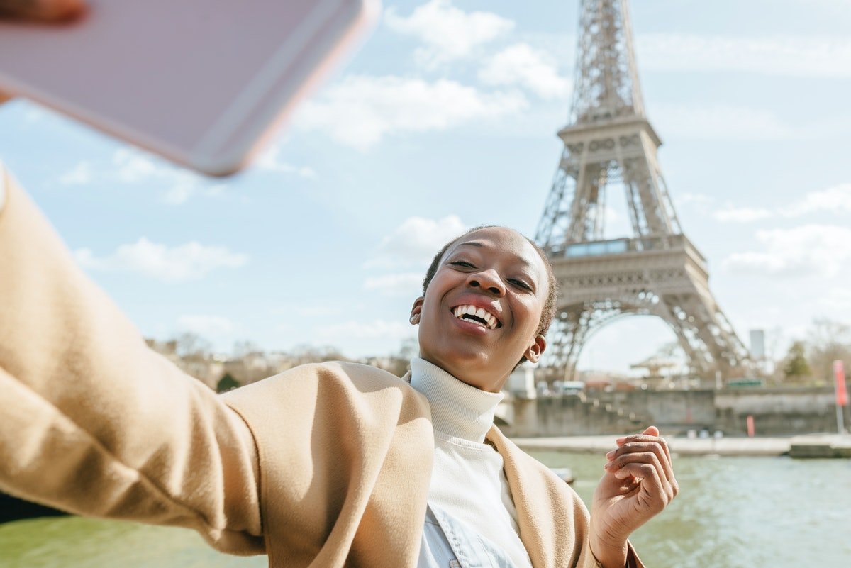 A young woman takes a vaxication selfie with the Eiffel Tower in Paris.