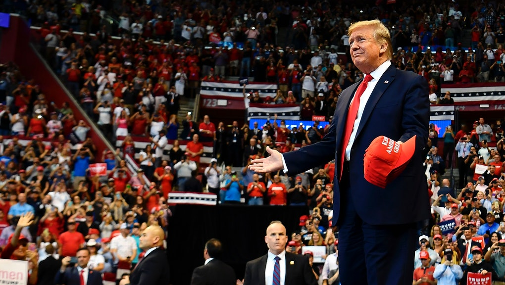 """US President Donald Trump throughs MAGA caps to supporters as he arrives for a """"Keep America Great"""" campaign rally at the BB&T Center in Sunrise, Florida on November 26, 2019. (Photo by MANDEL NGAN / AFP) (Photo by MANDEL NGAN/AFP via Getty Images)"""