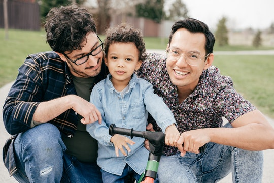 Two dads with toddler son having fun outdoor