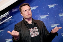 SpaceX owner and Tesla CEO Elon Musk (R) gestures as he arrives on the red carpet for the Axel Sprin...