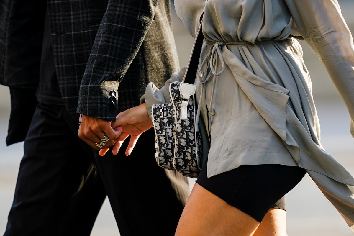 PARIS, FRANCE - JUNE 03: A woman wears a Dior monogram bag, and is holding the hand of a man, on Jun...