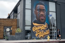 LOS ANGELES, CALIFORNIA - APRIL 21: A woman without a mask walks past a mural of George Floyd that r...