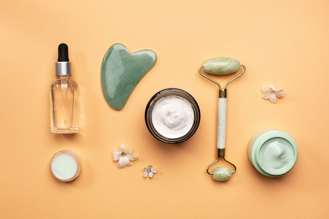 Flat lay of small flowers placed near jade spa tools and various natural cosmetic products on orange background