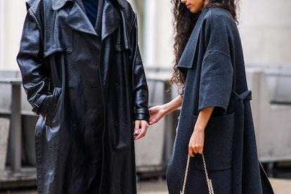 PARIS, FRANCE - FEBRUARY 29: A guest wears a gray coat and holds the hand of another guest who wears a black leather coat, outside Rokh, during Paris Fashion Week - Womenswear Fall/Winter 2020/2021, on February 29, 2020 in Paris, France. (Photo by Edward Berthelot/Getty Images)