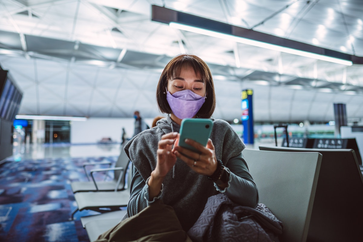 A young woman preps a vaxication selfie post on her phone while sitting in the airport.