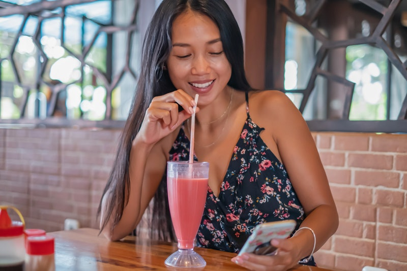 Front view shot of a smiling Indonesian woman using phone in a restaurant while waiting for her lunch.She's drinking watermelon juice with a straw