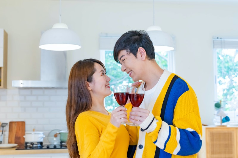 asian couple are looking at each other and smiling with red wine while celebrating anniversary in the living room at home