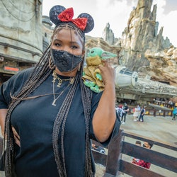 ANAHEIM, CALIFORNIA - MAY 21: In this handout photo provided by Disneyland Resort, Grammy Award-winning recording artist Lizzo, poses with Baby Yoda in front of the Millennium Falcon in Star Wars: Galaxy's Edge at Disneyland Park on May 21, 2021 in Anaheim, California.  (Photo by Christian Thompson/Getty Images via Disneyland Resort)