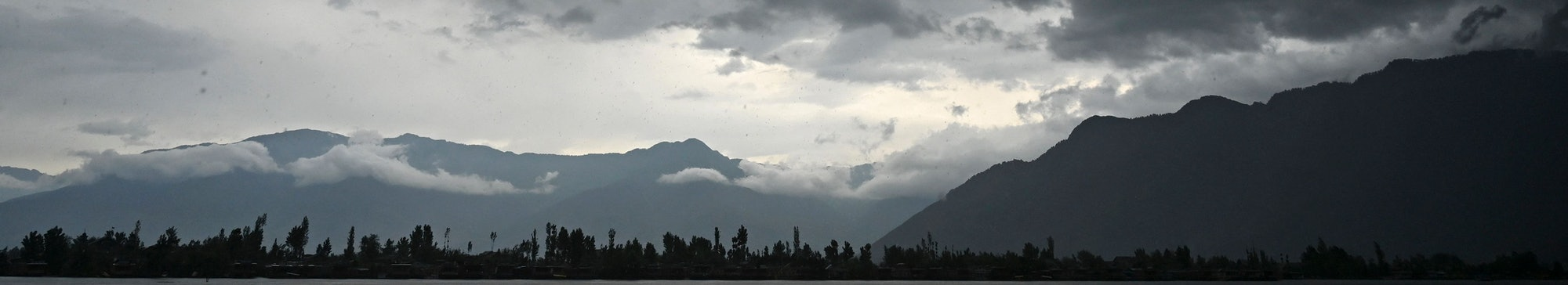 A man steers a boat as dark clouds loom over Dal Lake during a rainfall in Srinagar on June 1, 2021. (Photo by TAUSEEF MUSTAFA / AFP) (Photo by TAUSEEF MUSTAFA/AFP via Getty Images)