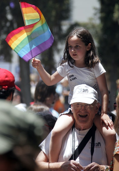 An Israeli girl sits on a relative's shoulders waving the rainbow flag, the international symbol of gay pride, during the annual Gay Pride parade along the streets of Tel Aviv.