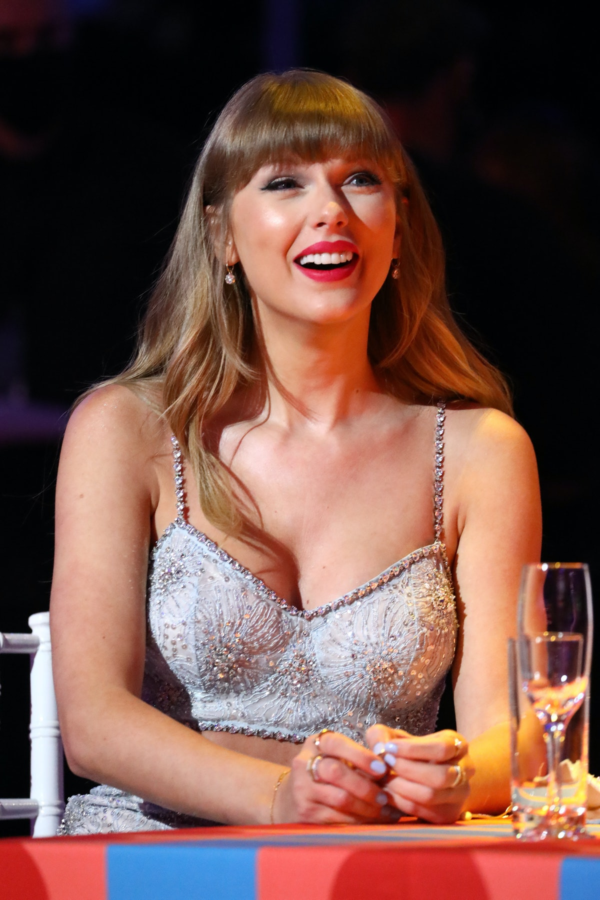 Taylor Swift wearing a sequined, beaded crop top and wearing her hair with blunt bangs at the BRIT A...