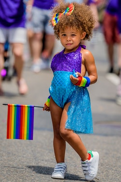 A girl holding a rainbow flag at the Pride March NYC.