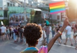 Rear view image of young African ethnicity woman walking at the LGBTQI pride event and waving rainbow flag