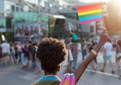 Rear view image of young African ethnicity woman walking at the LGBTQI pride event and waving rainbo...