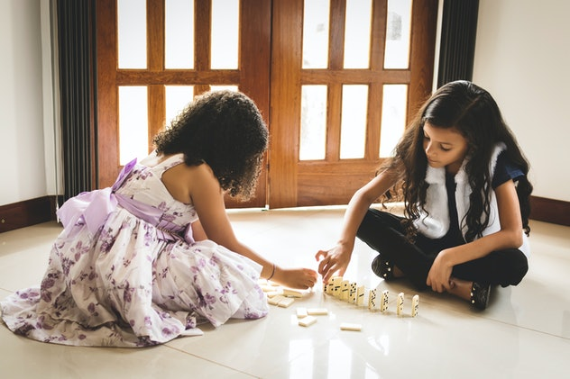 Two cute girls, about six years old, sitting on the floor and playing domino