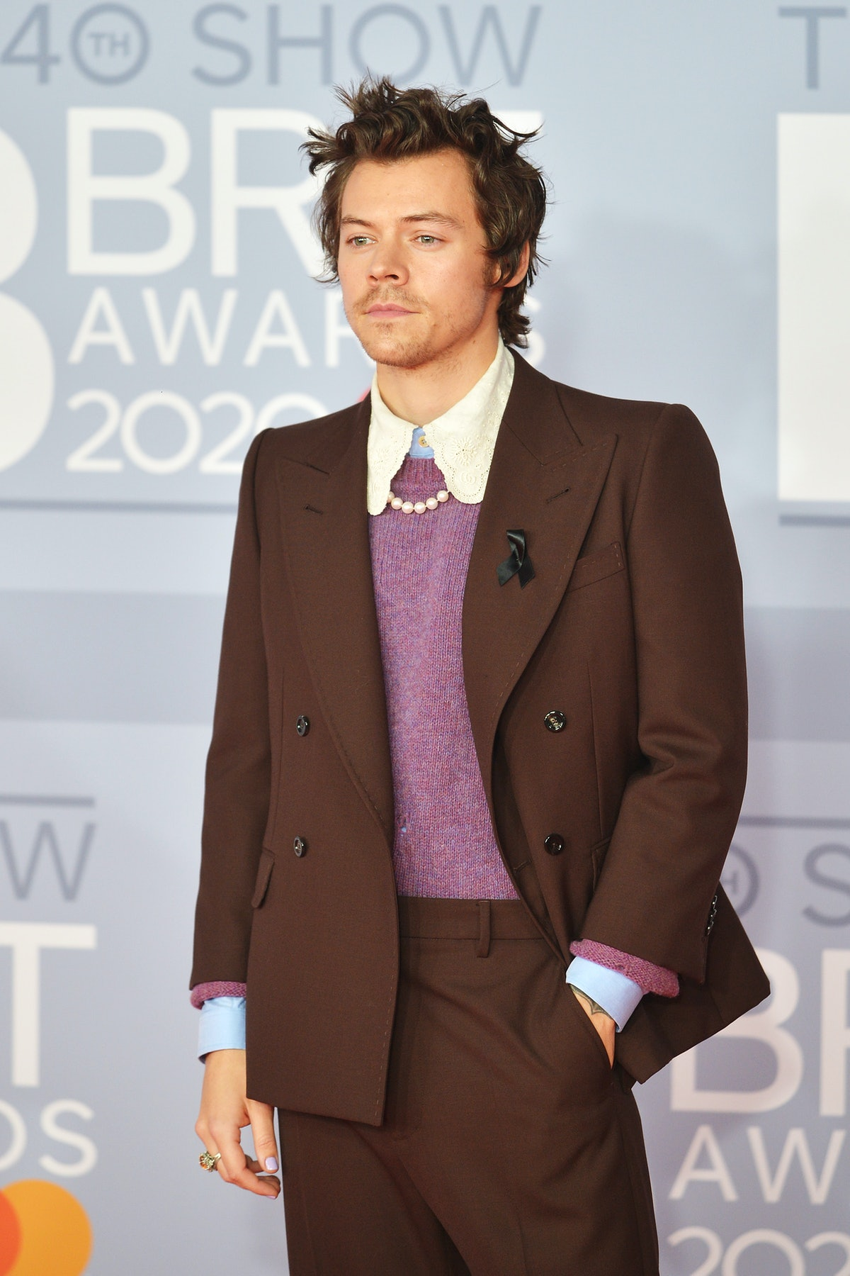 Harry Styles, who fans are convinced may be launching a perfume line, posing on the red carpet at the 2020 Brit Awards.