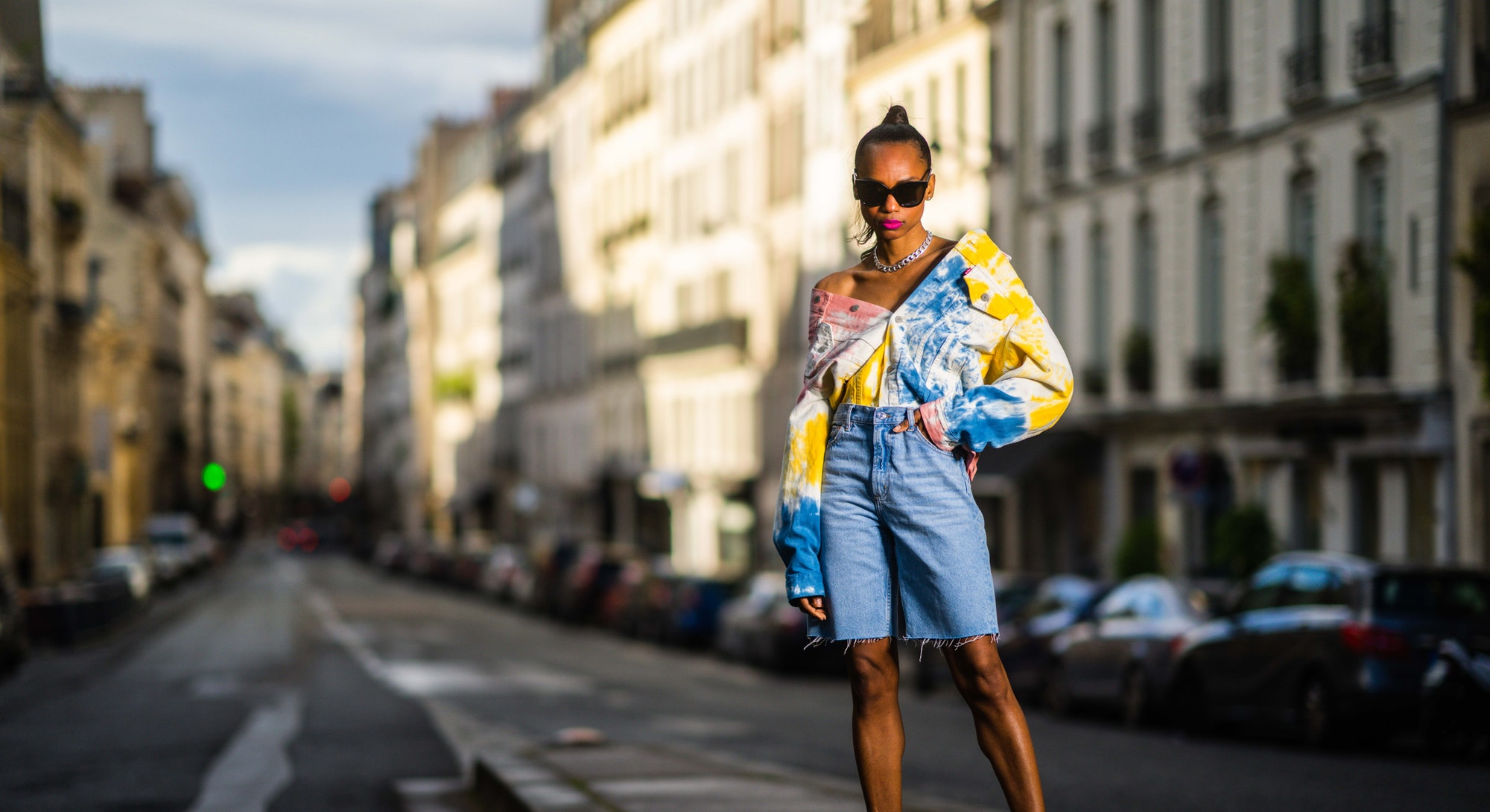 PARIS, FRANCE - MAY 21: Emilie Joseph @in_fashionwetrust wears diamond earrings, a silver chain necklace, black sunglasses, a white yellow blue and orange tie and dye denim jacket by Levis, a blue faded denim jean dad shorts by Mango, pointy pumps/ heels/ stilettos in pastel leather Jimmy Choo shoes, on May 21, 2021 in Paris, France. (Photo by Edward Berthelot/Getty Images)