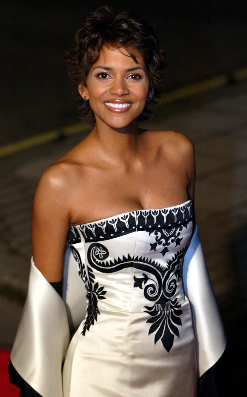 """US oscar-winner actress Halle Berry smiles upon arrival, 18 November 2002 for the Premiere of James Bond's film """"Die another Day"""" directed by New Zealand's Lee Tamahori at the Royal Albert Hall in London. The feature starring Pierce Brosnan as Bond for the fourth time opens on November 22nd. AFP PHOTO ODD ANDERSEN (Photo by Odd ANDERSEN / AFP) (Photo by ODD ANDERSEN/AFP via Getty Images)"""