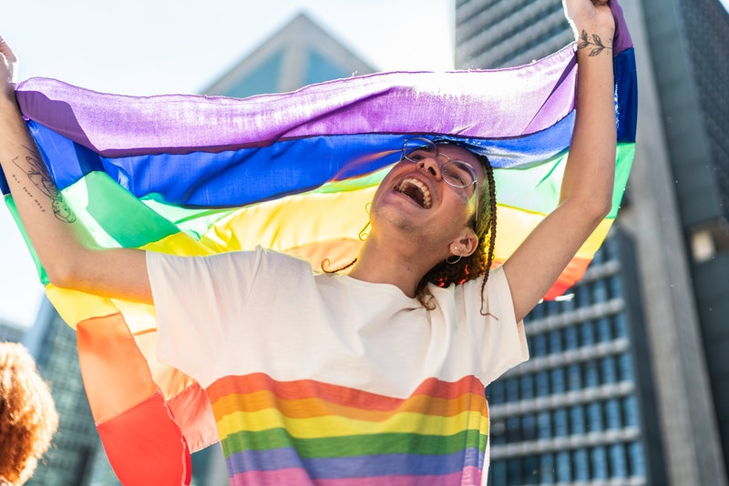 A queer person dances with multiple rainbow pride flags at a parade. Here's what the colors of different pride flags mean.