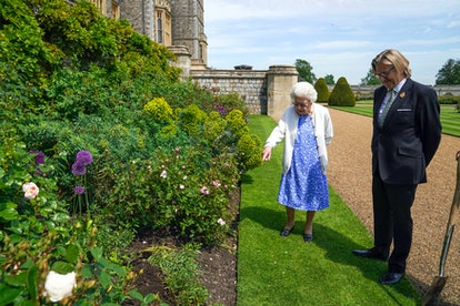 Britain's Queen Elizabeth II views a flower bed with President of the Royal Horticultural Society, Keith Weed, after he presented her with a Duke of Edinburgh rose, named in memory of her late husband Prince Philip, the Duke of Edinburgh, at Windsor Castle in Windsor, west of London, on June 2, 2021. - The newly bred deep pink commemorative rose from Harkness Roses has officially been named in memory of the Duke of Edinburgh. A royalty from the sale of each rose will go to The Duke of Edinburgh's Award Living Legacy Fund which will give more young people the opportunity to take part in the Duke of Edinburgh Award. (Photo by Steve Parsons / POOL / AFP) (Photo by STEVE PARSONS/POOL/AFP via Getty Images)