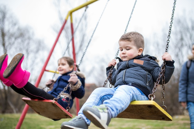 A family of three including a mother, son and daughter are having a day out in the park, playing on ...