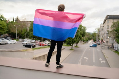 A bi woman holds up the bisexual pride flag: pink, purple, and blue.