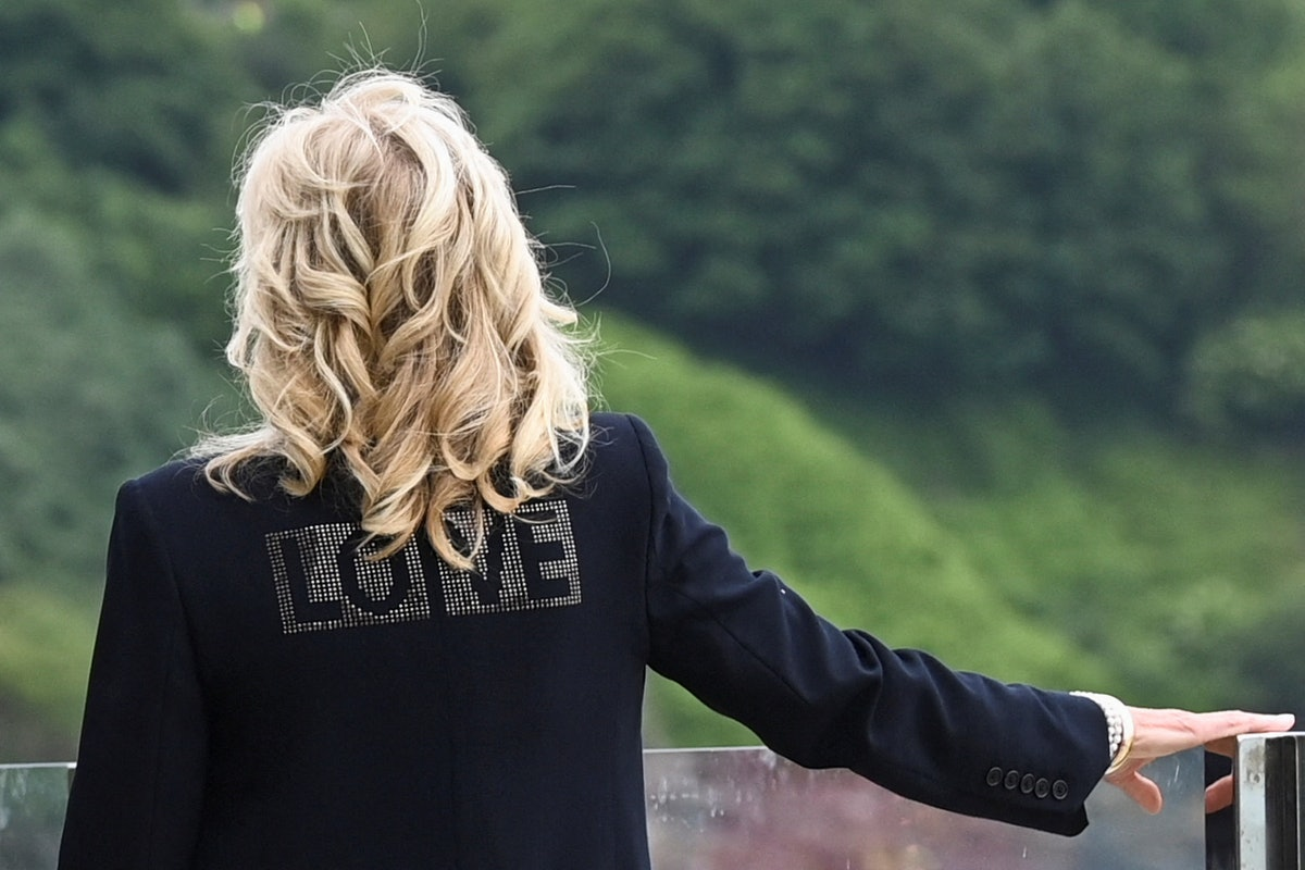 US First Lady Jill Biden, wearing a jacket with the words 'Love' on the back, looks out over the sea as she stands with US President Joe Biden and Britain's Prime Minister Boris Johnson and his wife Carrie Johnson (all unseen) prior to a bi-lateral meeting at Carbis Bay, Cornwall on June 10, 2021, ahead of the three-day G7 summit being held from 11-13 June. - G7 leaders from Canada, France, Germany, Italy, Japan, the UK and the United States meet this weekend for the first time in nearly two years, for the three-day talks in Carbis Bay, Cornwall. - (Photo by TOBY MELVILLE / AFP) (Photo by TOBY MELVILLE/AFP via Getty Images)