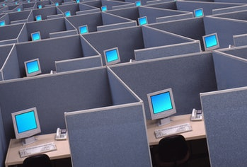 A vast expanse of cubicles and computers indicates the malaise of technology work, data input, and a dearth of creativity.
