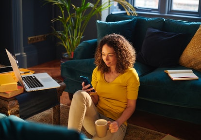A woman looks at her phone after being ghosted by a friend. If you want to confront a friend who ghosted you, a therapist recommends one of three approaches.