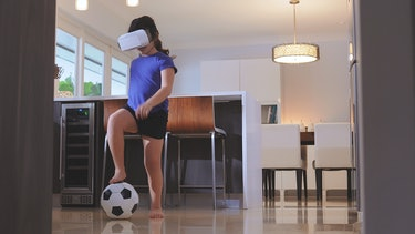 Little girl playing soccer using a Virtual Reality set