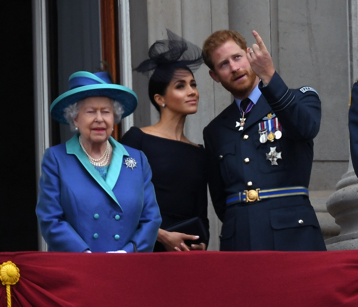 Queen Elizabeth ll, Meghan, Duchess of Sussex and Prince Harry, Duke of Sussex stand on the balcony of Buckingham Palace.