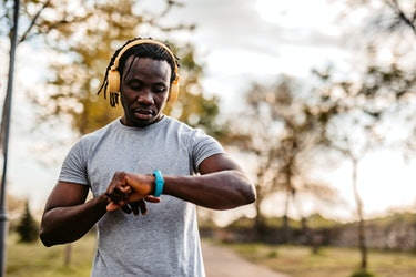 Athlete check fitness tracker on smartwatch or playing his music playlist after training in nature.